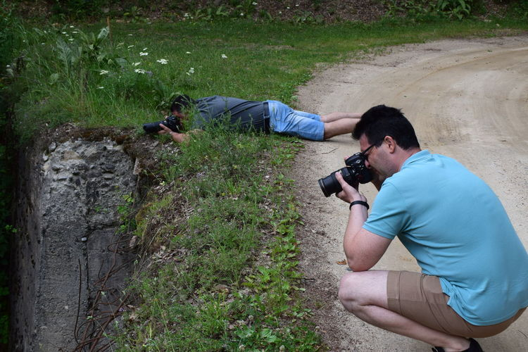 Men photographing on dirt road