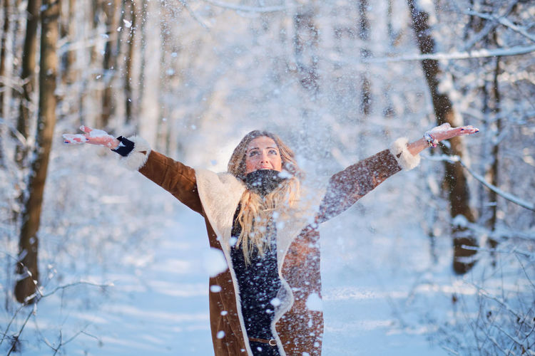Happy Woman Throwing Snow While Standing In Forest