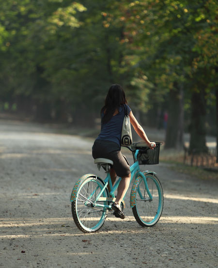 Woman cycling in a park of a city. Autumn City Exercise Summertime Transportation Woman Bicycle Cycling Girl Leisure Activity Mode Of Transport Nature One Person Outdoors Park - Man Made Space Real People Rear View Ride Riding Summer Transportation Urban Urban Cycling Urban Transportation Young Adult