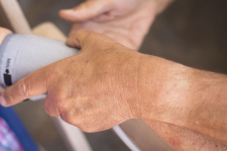 Cropped hands of doctor holding patient hand in hospital