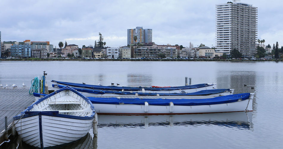 Boats moored on river by buildings against sky