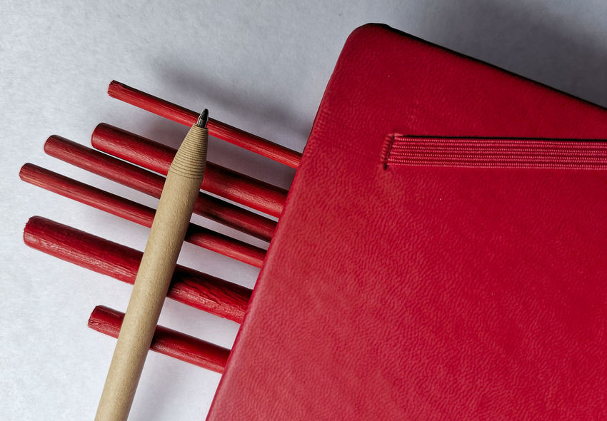 A pencil on the bamboo stick was clasped with a red book Red Indoors  No People Wood - Material Close-up Still Life High Angle View Wall - Building Feature Pattern Table Studio Shot Kitchen Utensil White Color Eating Utensil Group Of Objects Two Objects Art And Craft Order Fork Education