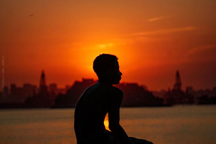 Silhouette man sitting at beach against orange sky