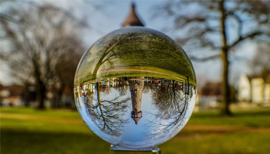 Reflection of tower on crystal ball at park
