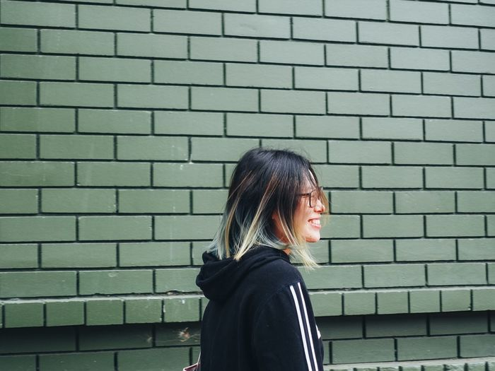 Side view of young woman standing against brick wall