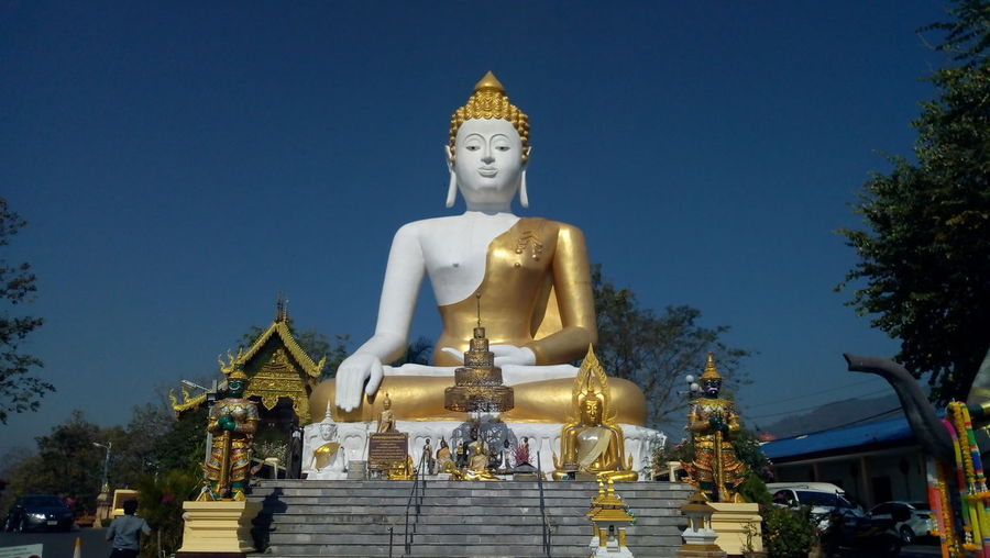Statue outside temple against building against sky