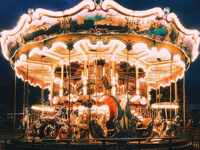 Low angle view of illuminated carousel in amusement park at night