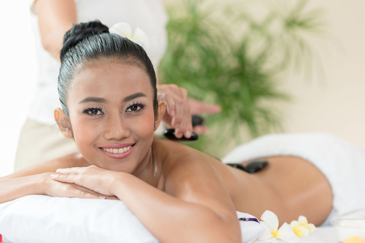 Portrait of smiling young woman being massaged by massage therapist in spa