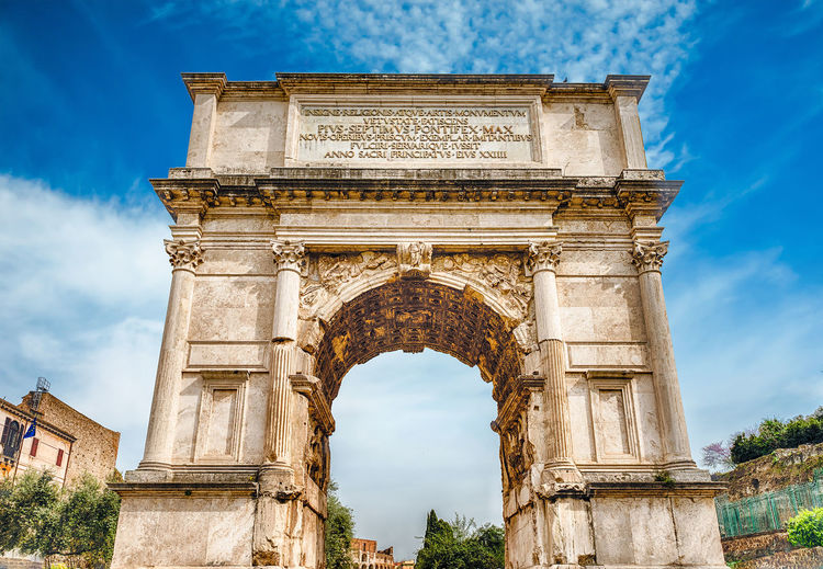 The iconic Arch of Titus on the Via Sacra in the Roman Forum, Rome, Italy Ancient Arch Architectural Column Architecture Art Blue Built Structure Capital Cities  Carving - Craft Product Cloud Cloud - Sky Cloudy Column Day Famous Place History Low Angle View Monument No People Ornate Outdoors Sky The Past Tourism Travel Destinations