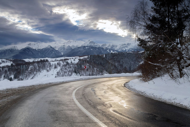 Road by snow covered mountains against sky