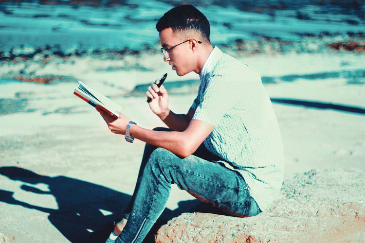 One Person Real People Lifestyles Communication Leisure Activity Holding Wireless Technology Casual Clothing Sitting Mobile Phone Technology Focus On Foreground Beach Men Water Portable Information Device Outdoors Relax