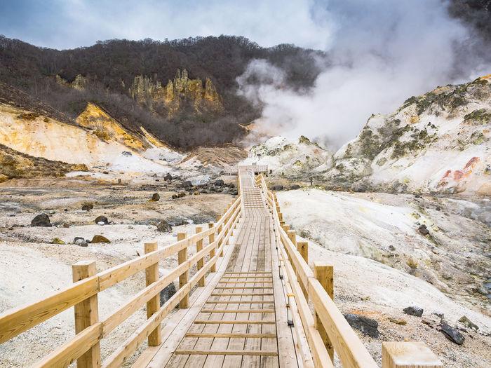 Footbridge leading towards smoke at mountain