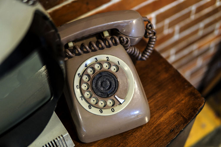 Vintage Telephone On Table Against Brick Wall