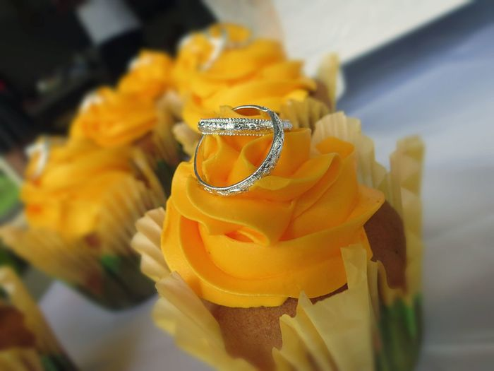 Close-up of wedding rings on fresh yellow cupcake