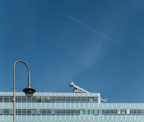 Low angle view of street light and building against blue sky