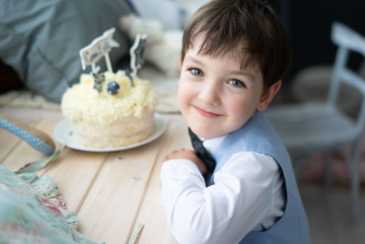 Portrait of cute boy with cake on table