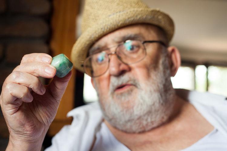 Close-up of senior man looking at pebble