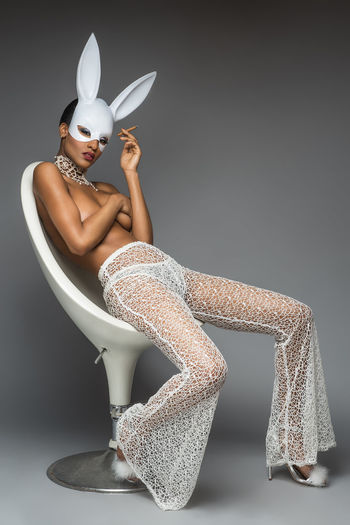 Portrait of young woman wearing rabbit costume against gray background