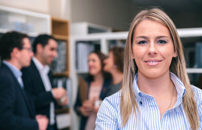 Portrait of smiling blonde woman looking at camera in the office with colleagues talking on background Business Company Horizontal Innovation Man Meeting Office Teamwork Woman Working Workplace Business Finance And Industry Businessman Businesspeople Businesswoman Colleague Connection Group Headquarters Leadership Networking People Sharing  Success Team