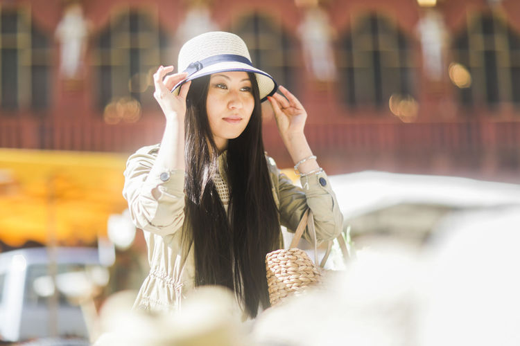 Young woman wearing hat standing against blurred background