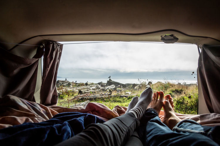 Low section of couple relaxing in camper van