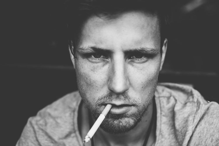 Close-up portrait of man smoking cigarette