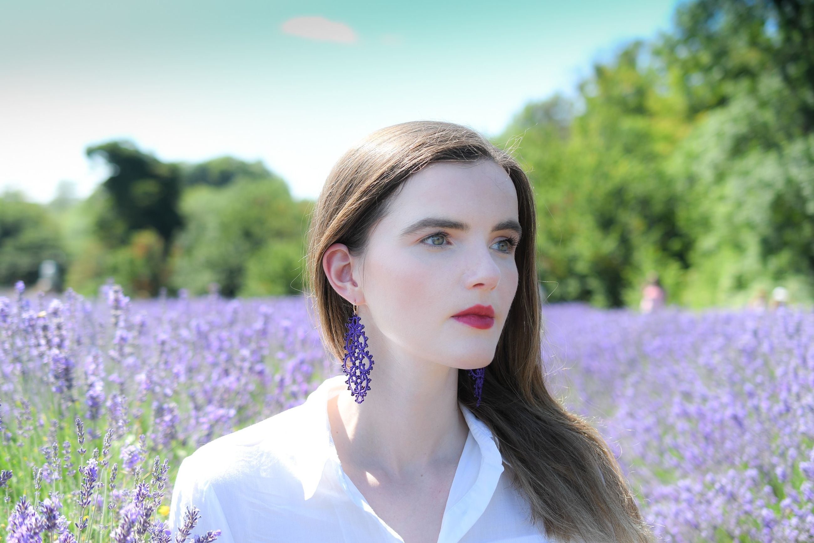 young adult, young women, plant, portrait, flower, one person, real people, flowering plant, field, headshot, lifestyles, front view, hairstyle, nature, leisure activity, growth, beauty, land, long hair, beautiful woman, hair, purple, outdoors