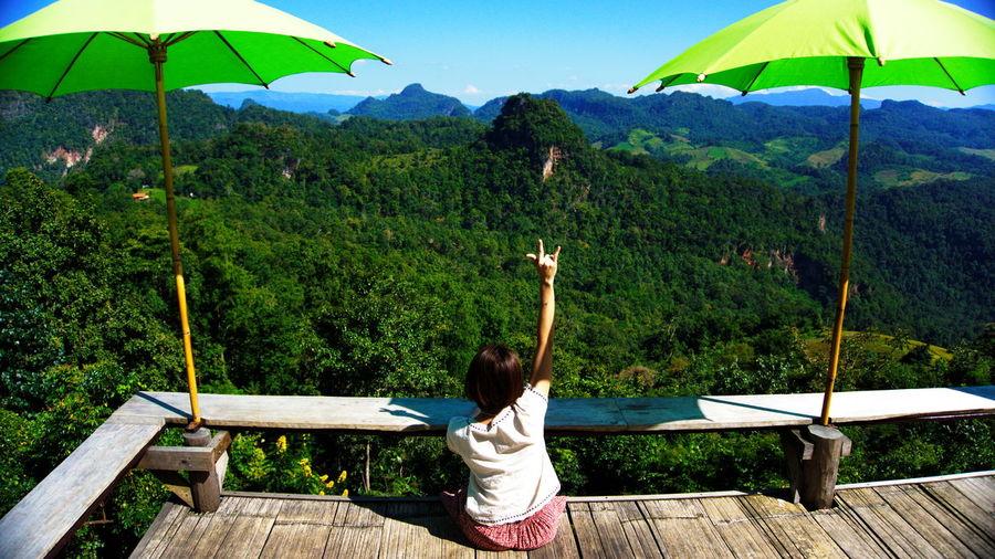 Woman gesturing while sitting on footbridge against blue sky