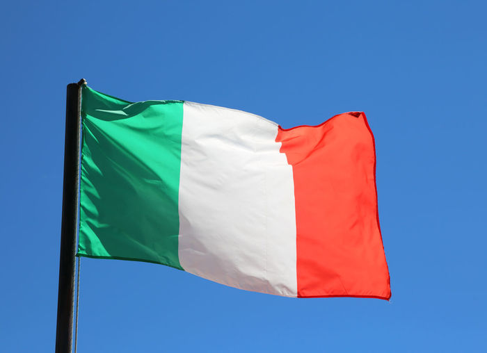 Big italian flag waving in blue sky with vivid red and white green colors