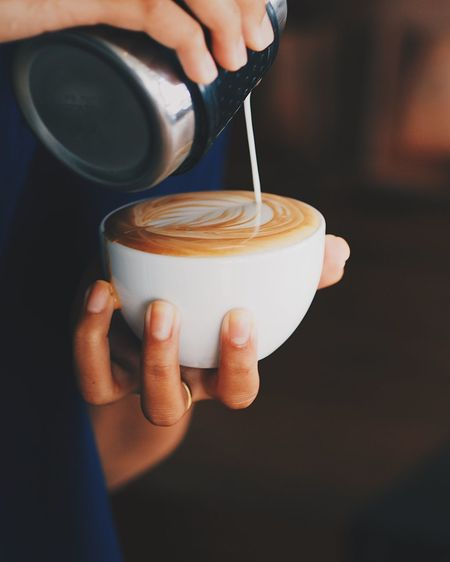 Coffee latte art by coffee master in coffee shop. Cafe Cappuccino Close-up Coffee - Drink Coffee Cup Cup Day Drink Food And Drink Freshness Froth Art Frothy Drink Holding Human Body Part Human Hand Indoors  Latte Mocha One Person People Real People Refreshment Table Women