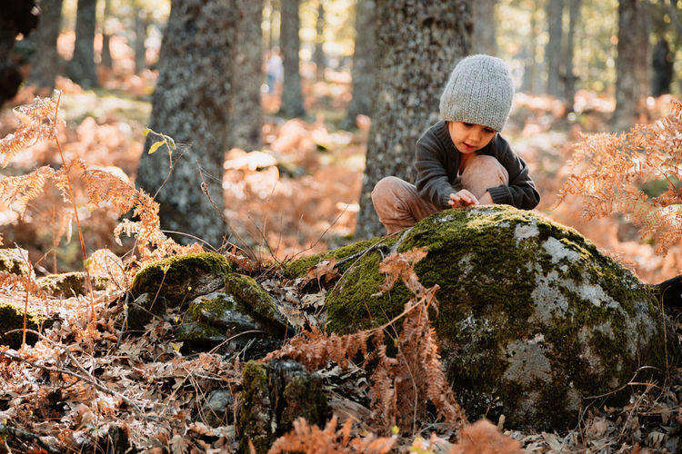 Girl crouching on rock with moss in forest