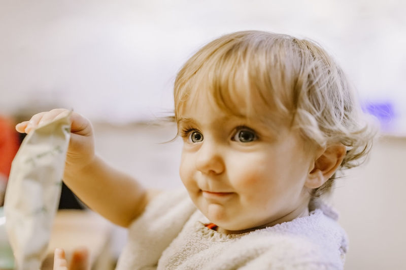 Close-up of cute baby girl holding packet