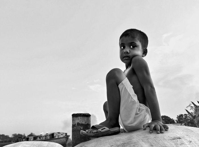 Boy looking away sitting against sky