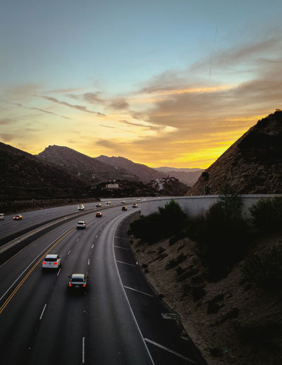 Aerial view of highway against sky during sunset