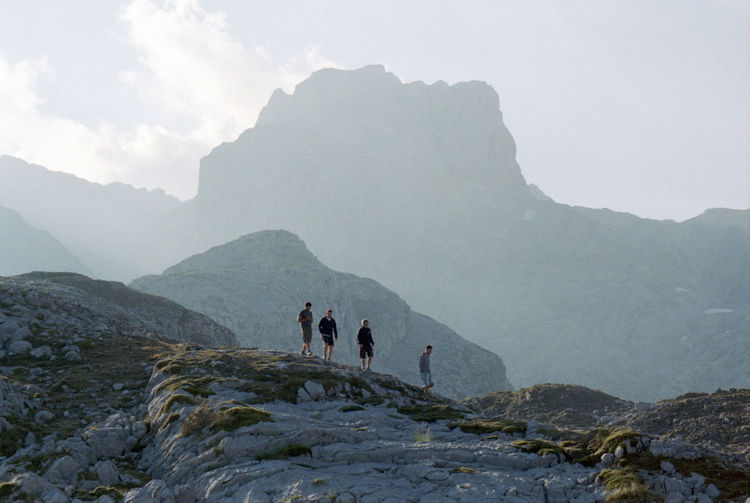 Low Angle View Of Male Friends Walking On Mountain Against Sky