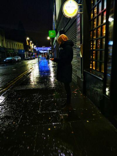 Woman walking on wet street at night
