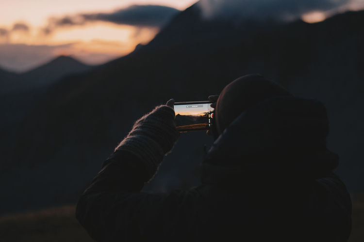 Midsection of man photographing at sunset