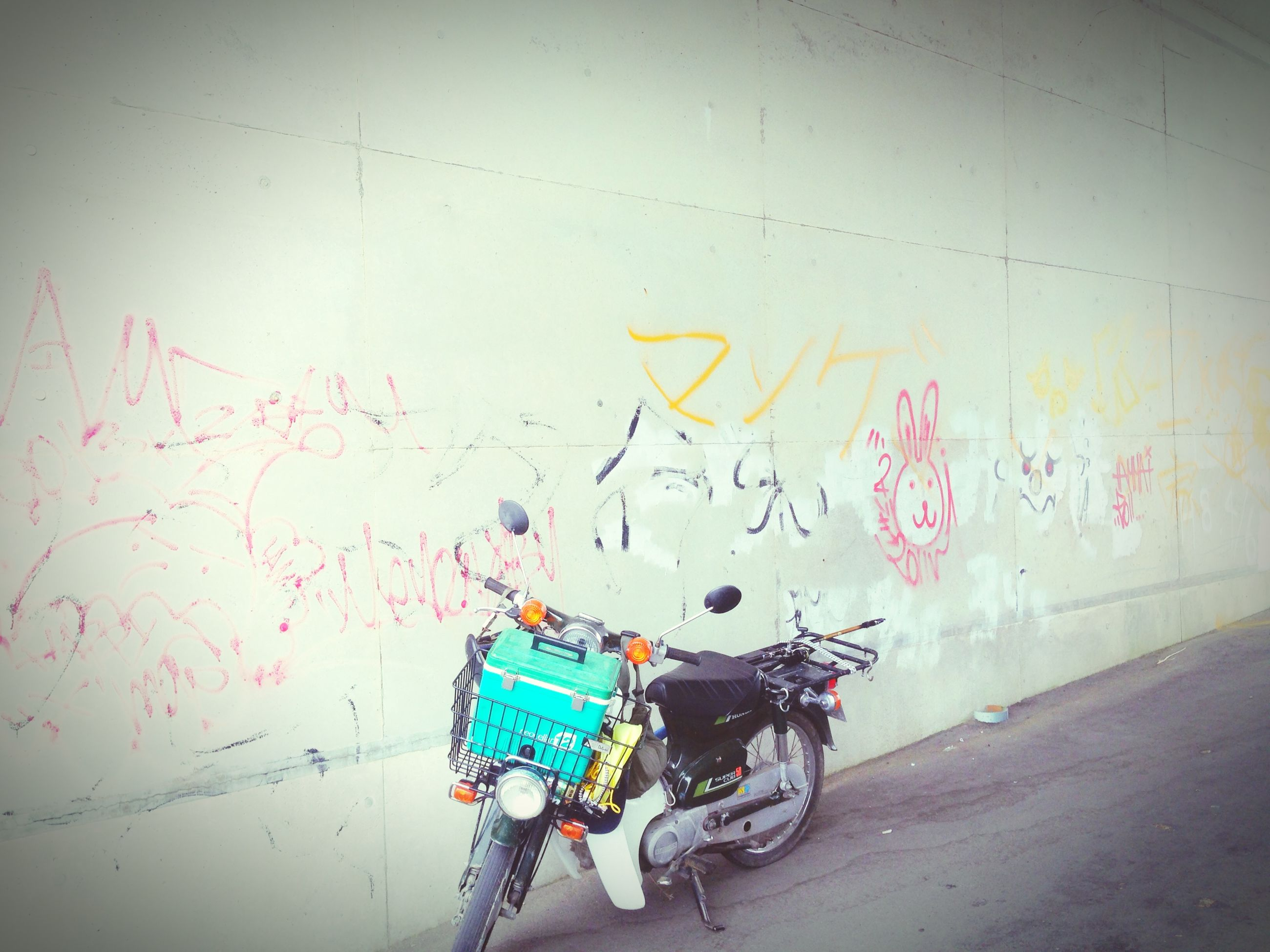 bicycle, text, transportation, graffiti, wall - building feature, communication, western script, mode of transport, land vehicle, stationary, wall, parked, parking, street, day, riding, sign, men, outdoors