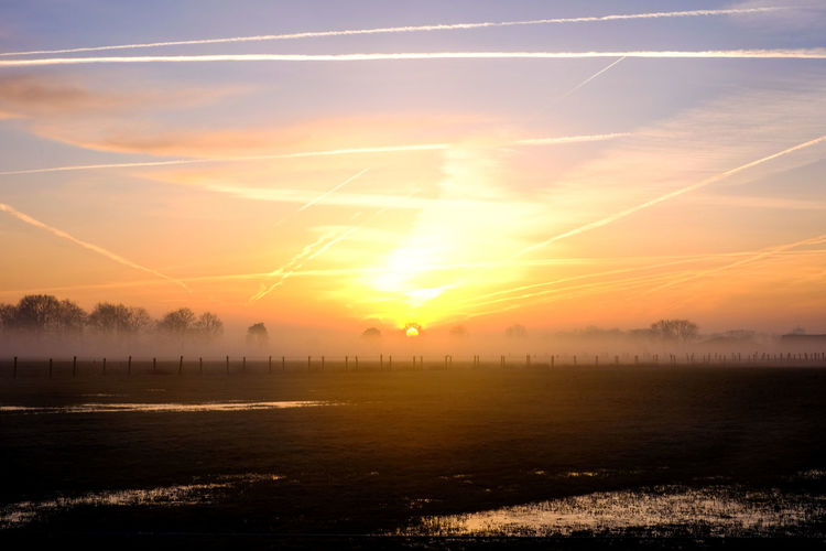 Countryside winter sunrise landscape Beauty In Nature Cloud - Sky Hazy  Idyllic Lake Nature No People Non-urban Scene Orange Color Outdoors Reflection Scenics - Nature Silhouette Sky Sun Sunlight Sunset Tranquil Scene Tranquility Vapor Trail Water Waterfront