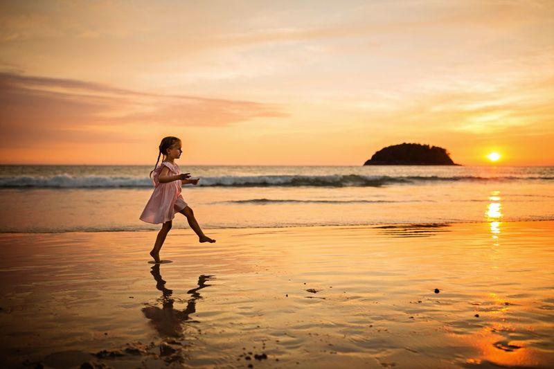 Full length of girl walking at beach against sky during sunset