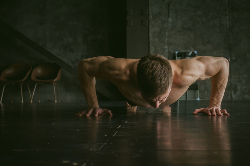 Shirtless Young Man Doing Push-Ups In Gym