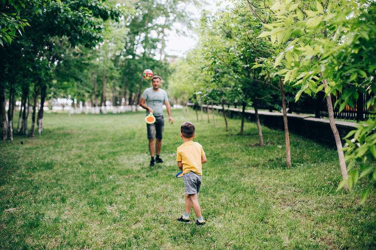 Full length of father and son playing on grass against trees