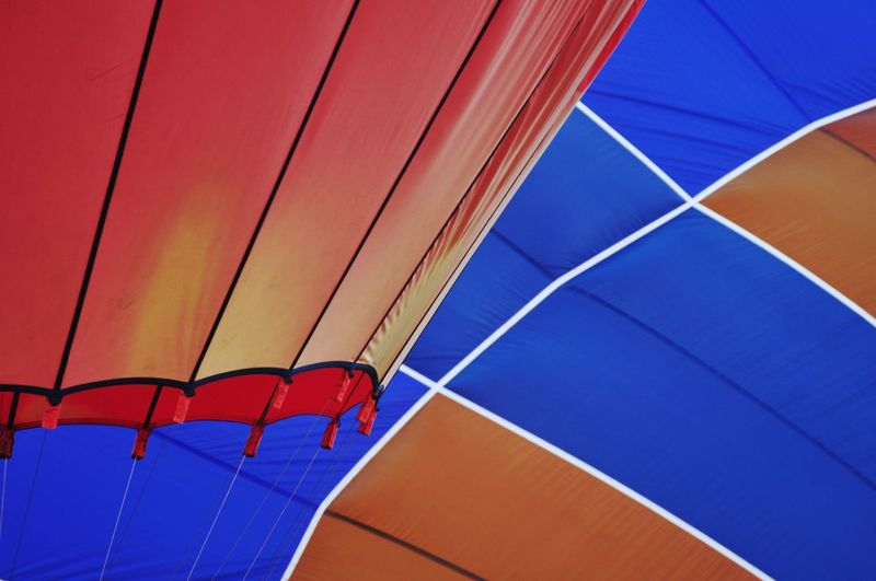 Low angle view of multi colored balloons against blue sky