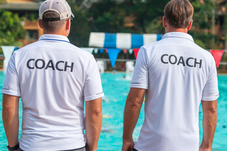 Rear view of men wearing t-shirts with coach text standing by swimming pool