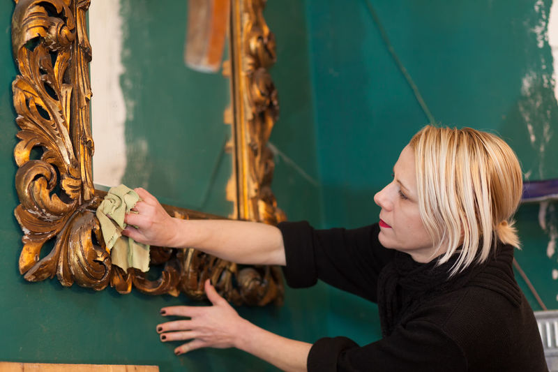 woman cleaning a mirror in preparation for auction Auction Decor Golden Green Wall Home Mirror Woman Worker Workshop Art Background Blond Hair Close-up Decoration Frame Furniture Indoors  People person Preparing Professional Real People Restore Restoring Texture