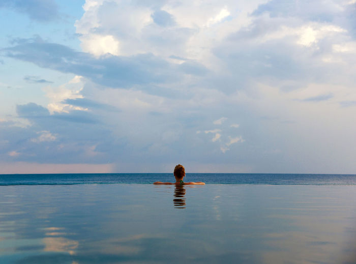 Beach Beauty In Nature Blue Calm Cloud Cloud - Sky Horizon Over Water Idyllic Infinity Infinity Pool Nature Ocean One Woman Only Rear View Reflection Relaxation Remote Scenics Sea Sky Solitude Tranquil Scene Tranquility Vacations Water