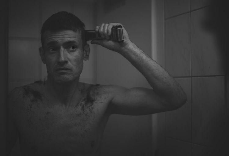 Shirtless man doing haircut in bathroom