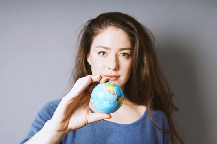 Holding Portrait Looking At Camera One Person Gray Background Studio Shot Indoors  Long Hair Young Adult Casual Clothing Brown Hair Young Women Beautiful Woman World Globe Earth Travel Concept Environment Female Woman Real People America Planet Girl Selective Focus
