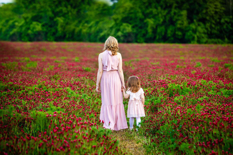 Rear view of women with pink flowers on field