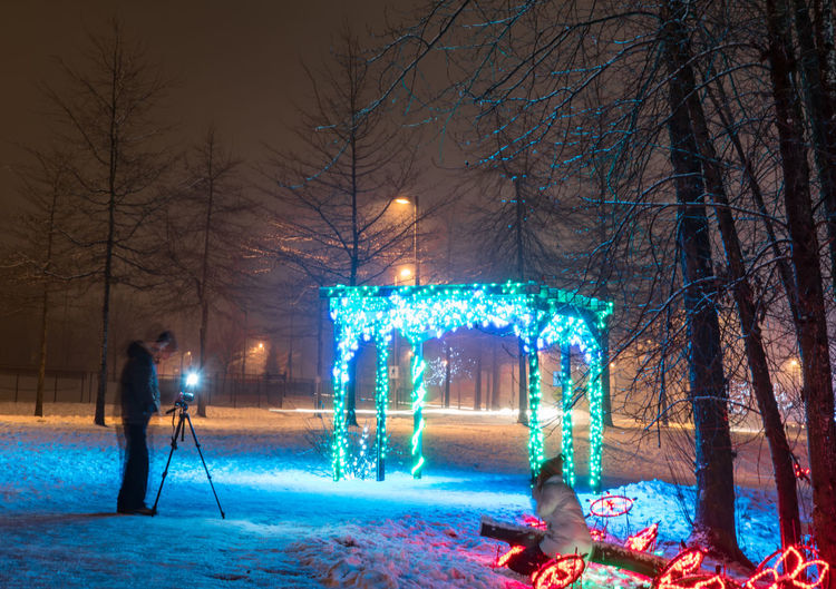 Adult Adults Only Bare Tree Christmas Christmas Decoration Christmas Lights Christmas Tree Cold Temperature Full Length Illuminated Motion Night One Person Outdoors People Photographer At Midnight Tree Winter